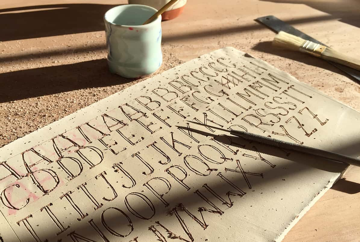 Horie drawing letters using the sgraffito technique