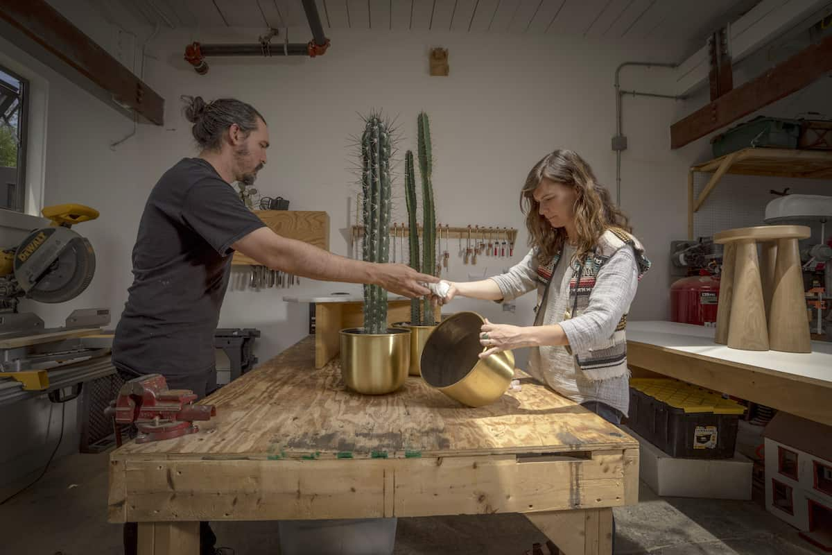 Ben (left) and Aja Blanc in their Providence, Rhode Island, design studio with their brass planters | photo by Ian Travis Barnard