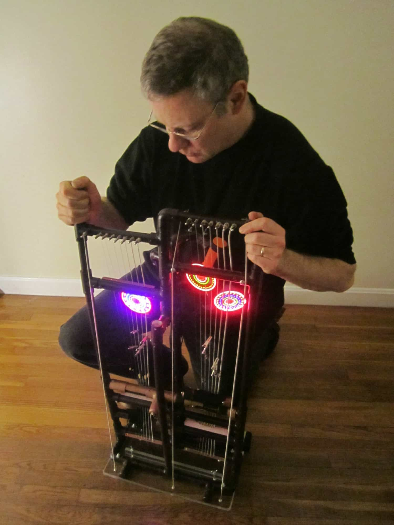 """This string assembly is played by a series of battery powered glowing fans. When the structure is twisted, the fans strike various points on the instrument. This creates a large variety of sounds."" 