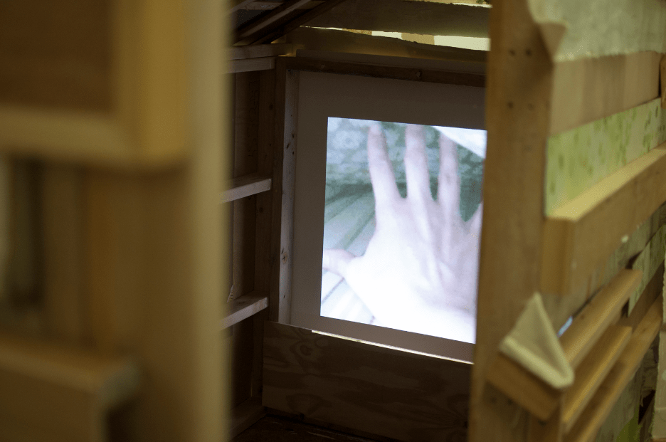 "Inside shot of Love Shack instillation featuring video loop of ""Waking Up And Getting Up Has Never Been Easy"", installation and video by Coe Lapossy 