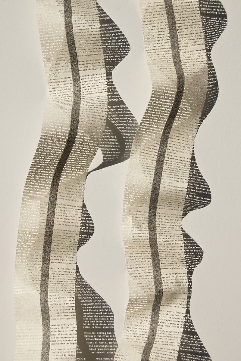 Youdhi Maharjan, Of Murmuring Streams, 2017, text cutout on book pages, 40 x 3.35 in. each. Photo by Youdhi Maharjan