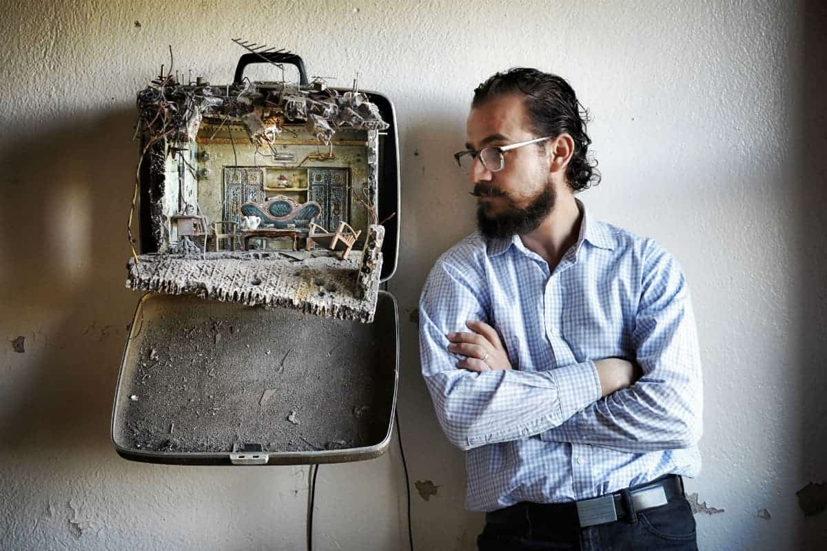 Mohamad Hafez considers Unpacked Refugee Baggage: Ayman & Ghena, 2017, mixed media. Photo by Paul Specht